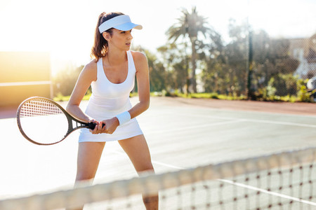 Female tennis player with racket at the tennis court