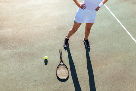 Sportswoman with racket and ball on tennis court