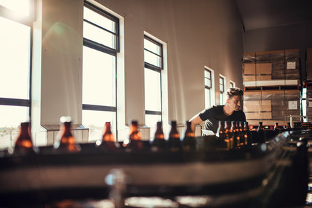 Man supervising the production of craft beer at brewery
