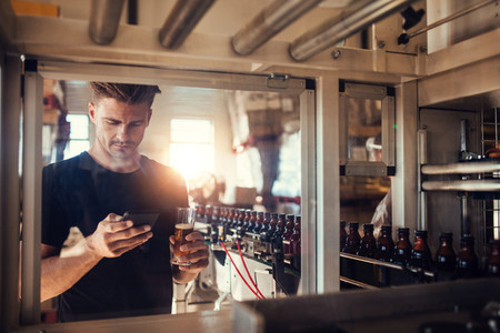 Young man at brewery plant using mobile phone