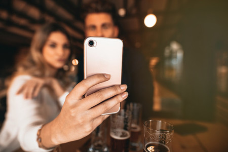 Couple sitting in the bar and taking a selfie