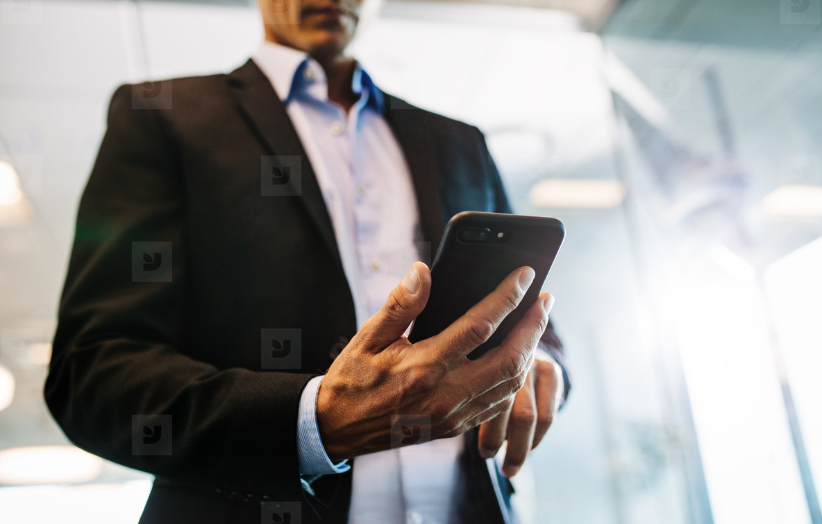 Businessman reading ext message on smart phone