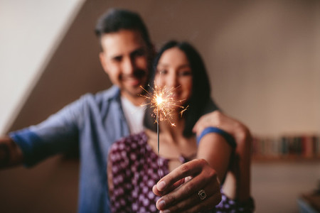 Young couple celebrating with sparkler at home