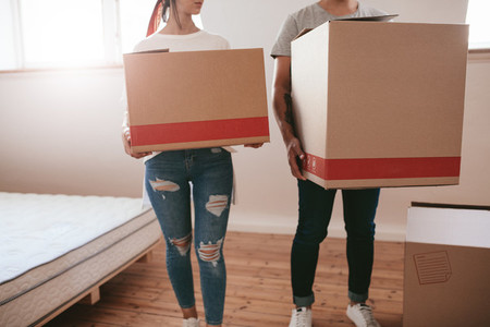 Couple with big cardboard boxes moving to new place