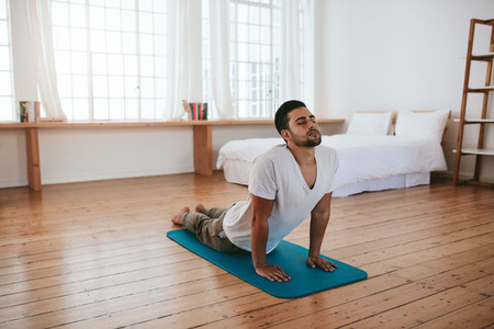 Healthy young man practicing yoga at home