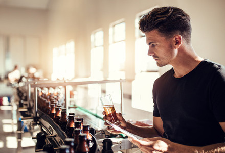 Male manufacturer testing beer in the microbrewery