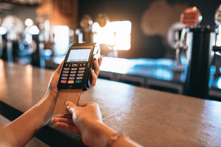Hands of woman doing cashless payment at bar