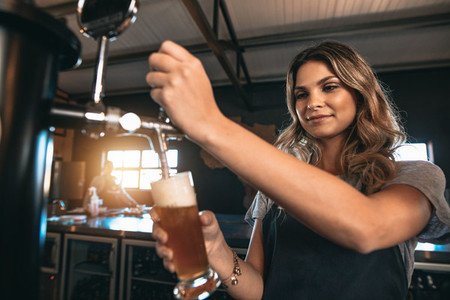 Beautiful female bartender tapping beer in bar