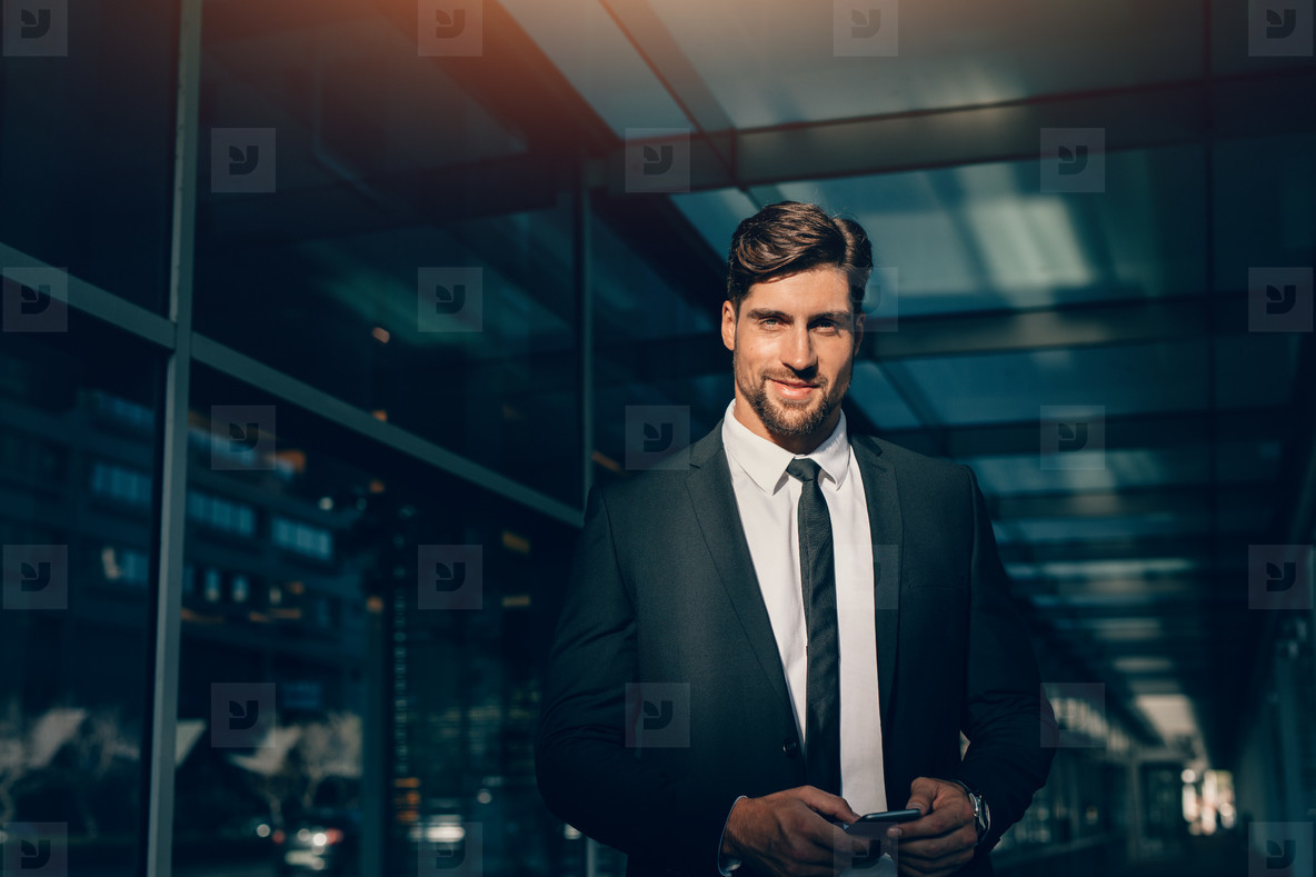 Handsome young businessman looking at camera and smiling