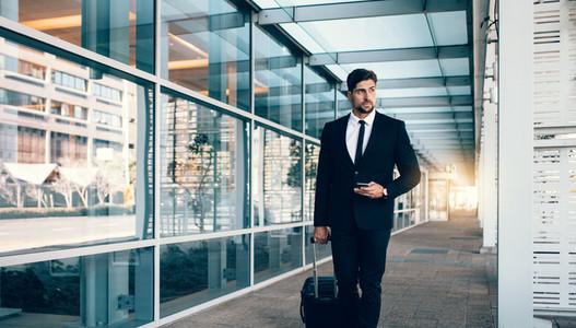 Business traveler with suitcase at airport