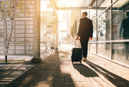 Businessman walking with bag outside airport