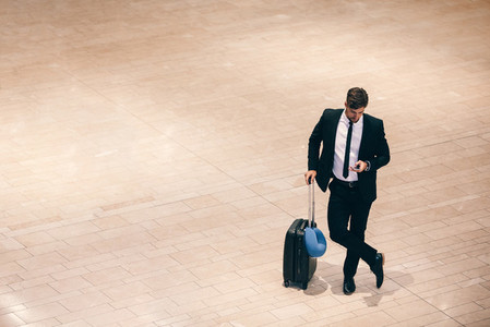 Businessman at airport terminal with suitcase and mobile phone