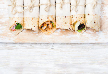 Tortilla wraps with various fillings on shabby white wooden board