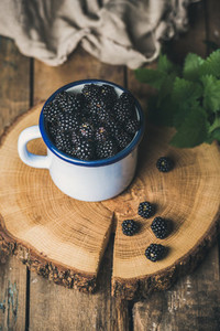 Fresh garden Blackberries in white cup on round serving wooden