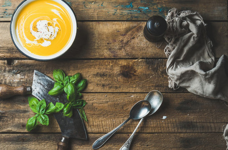 Pumpkin cream soup in bowl with fresh basil and spices