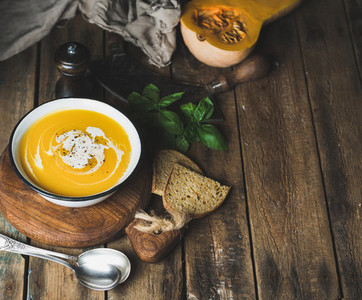 Pumpkin cream soup in bowl with basil spices and bread