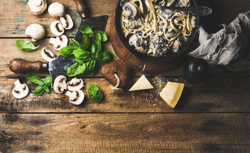 Creamy mushroom pasta spaghetti in cast iron pan with basil