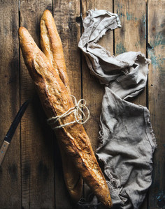 Two French baguettes on rough rustic wooden background