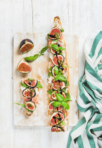 Long baguette sandwich with prosciutto  mozzarella  arugula  figs  basil  balsamico