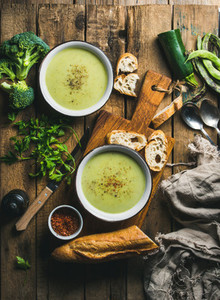 Two bowls of homemade pea  broccoli and zucchini cream soup