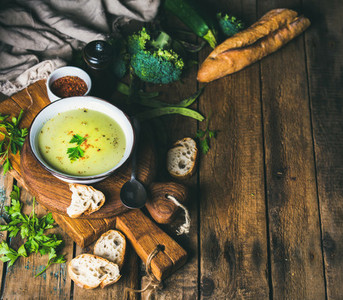Homemade pea broccoli zucchini cream soup with baguette copy space