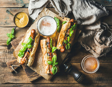 Wheat unfiltered beer and grilled sausage dogs in baguette