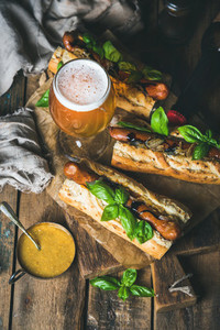 Glass and bottle of unfiltered beer  grilled sausage dogs