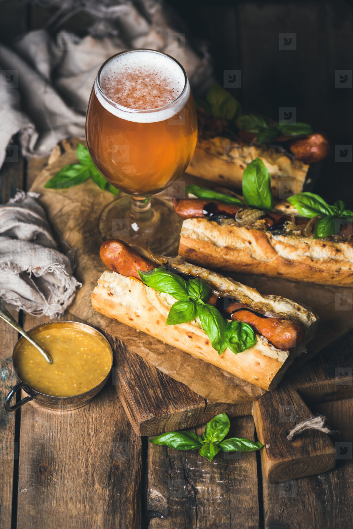 Glass of wheat beer and grilled sausage dogs in baguette