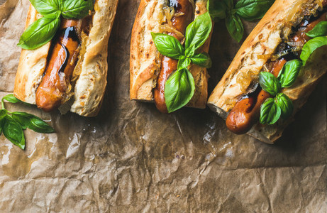 Homemade grilled sausage dogs in baguette on baking paper