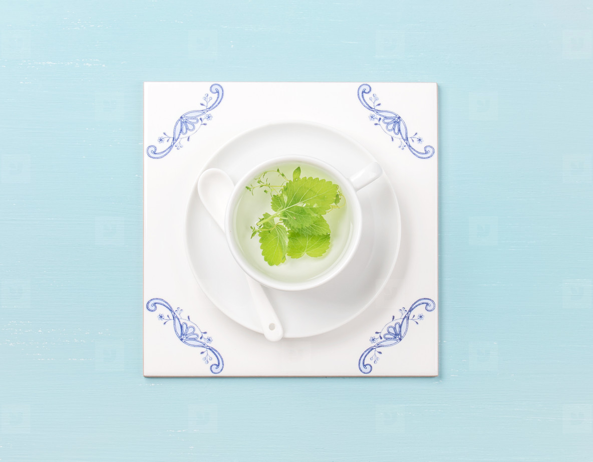 Cup of tea on white tile board over sky blue background