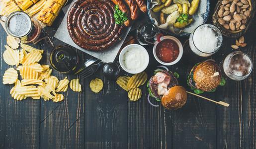Variety of beers  sausages  burgers  potato  corn on dark background