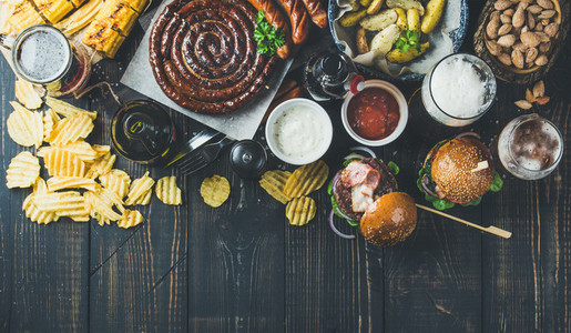 Variety of beers  sausages  burgers  potato  corn on dark background