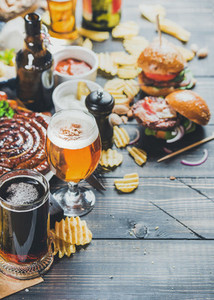 Octoberfest beer and snacks set on dark scorched wooden background