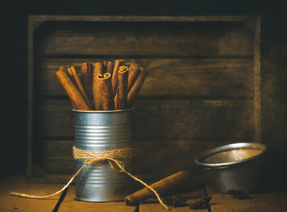 Cinnamon sticks in tin can rustic wooden background copy space