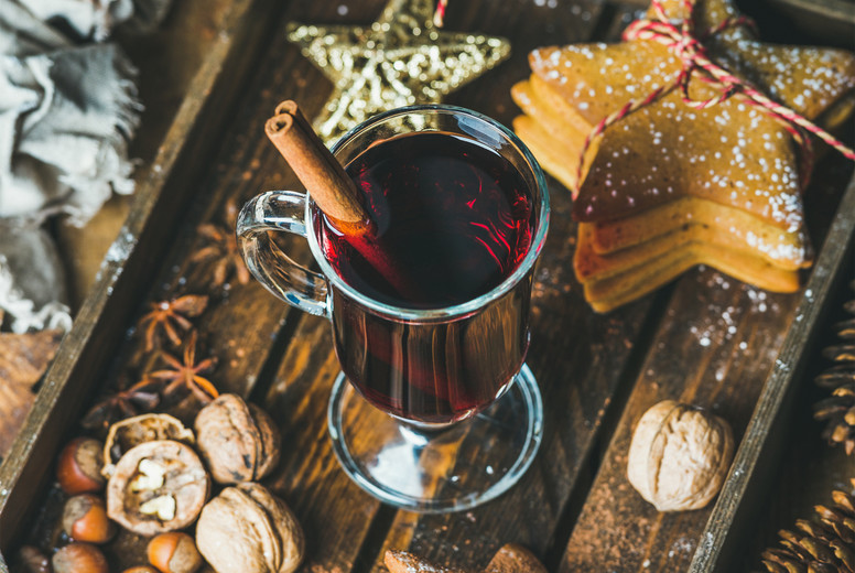 Glass of mulled wine  gingerbread cookies  spices in wooden tray