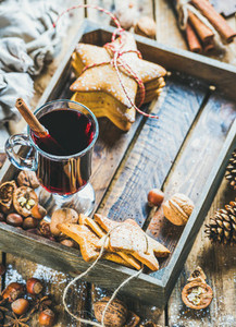 Glass of mulled wine gingerbread cookies and spices copy space
