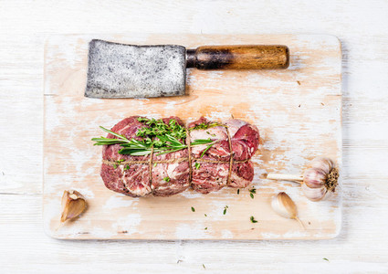 Raw roastbeef meat cut with herbs over white wooden background