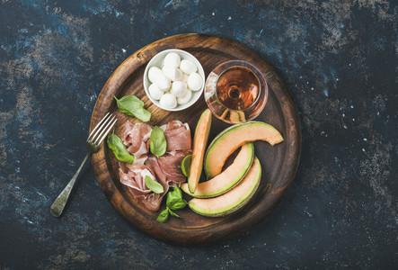 Prosciutto  cantaloupe melon  basil  mozzarella and glass of rose wine
