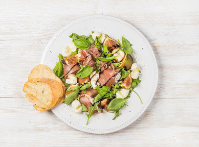 Prosciutto  arugula  basil  figs salad and glass of red wine