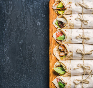 Tortilla wraps with various fillings on dark grey concrete background