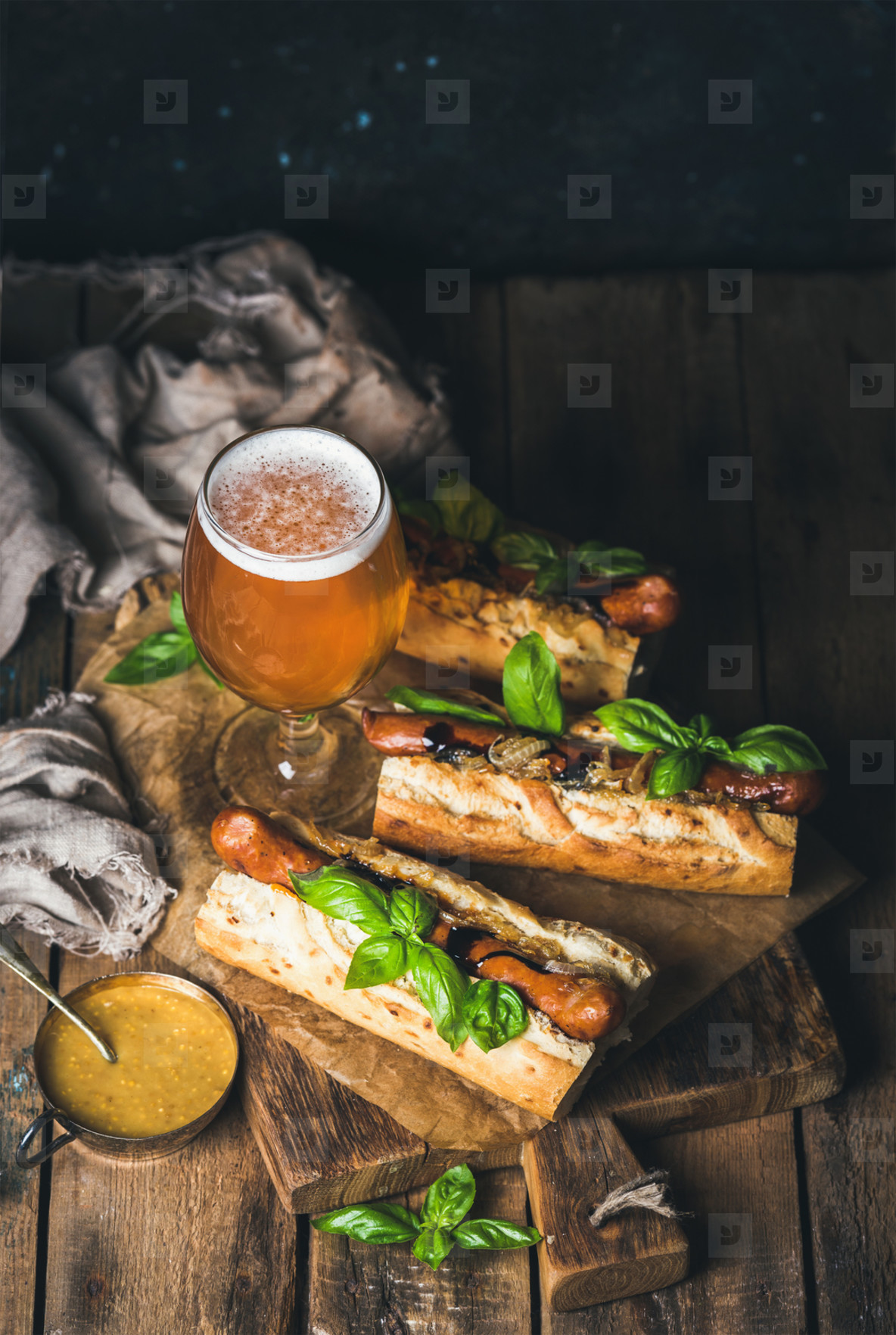 Glass of unfiltered beer and grilled sausage dogs in baguette