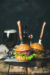 Beef burger with crispy bacon and glass of dark beer