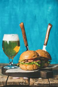 Beef burgers with crispy bacon  vegetables and glass of beer