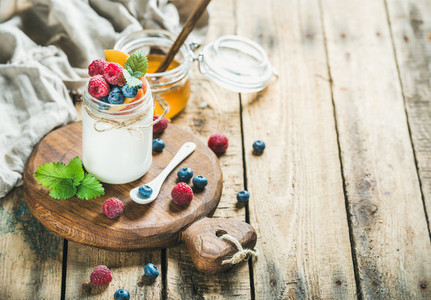 Glass jar of yogurt with berries mint and honey
