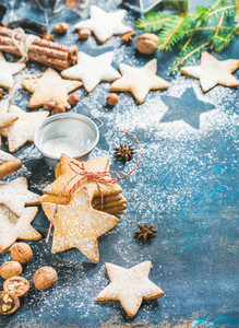 Star shaped cookies with spices sugar powder and fir tree branch
