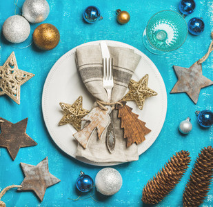 Christmas New Year holiday table setting over bright blue background
