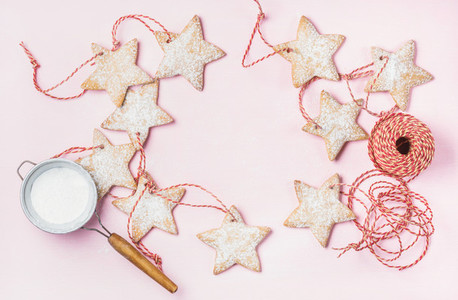 Christmas gingerbread star shaped cookies with sugar powder in sieve