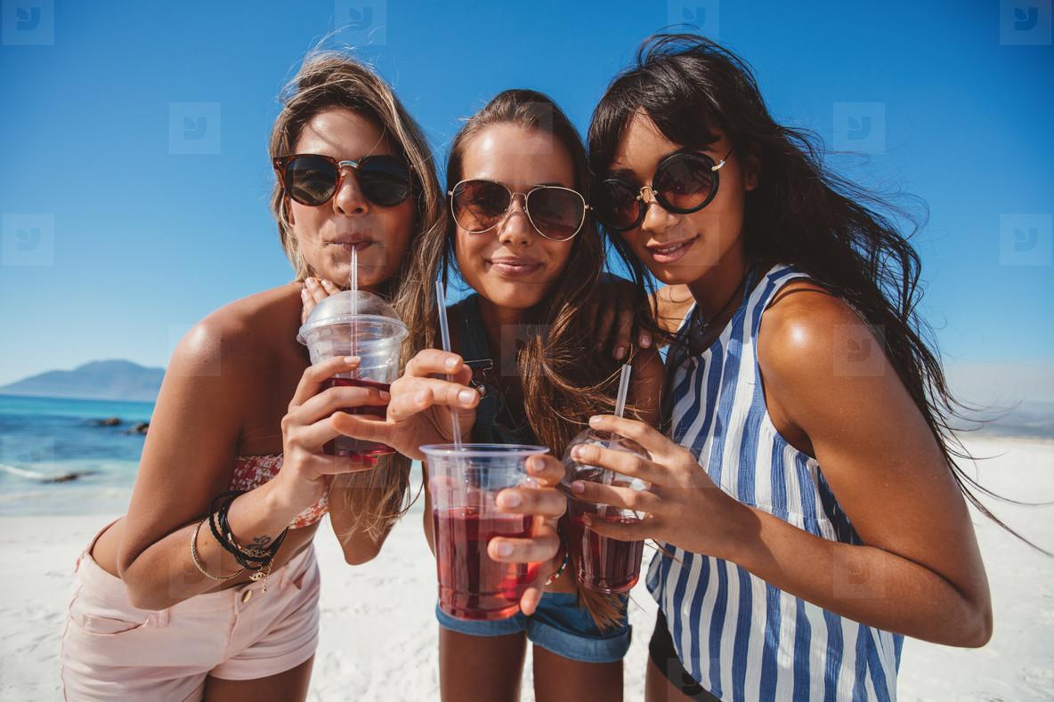 Girlfriends drinking ice tea on the beach