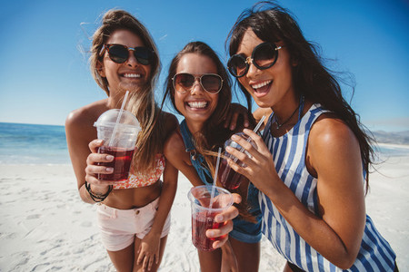 Three young women enjoying ice tea on seashore