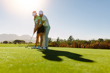 Male golf instructor teaching female golf player